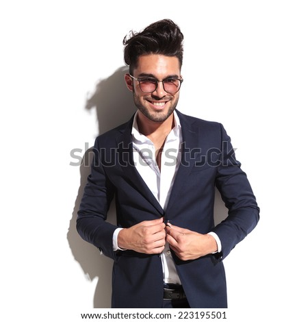 Smiling business man unbuttoning his jacket while leaning on a white wall, looking at the camera - stock photo