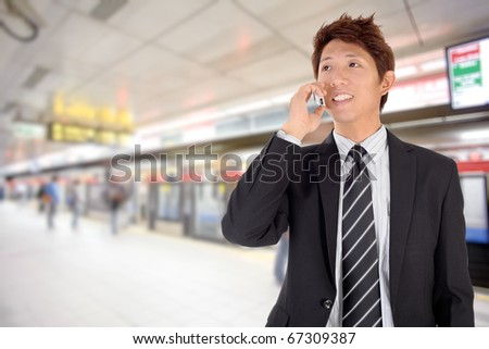 Smiling business man using cellphone in station. - stock photo