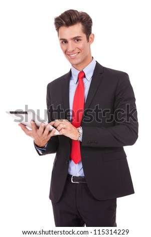 smiling business man using his tablet pad and looking at the camera - stock photo