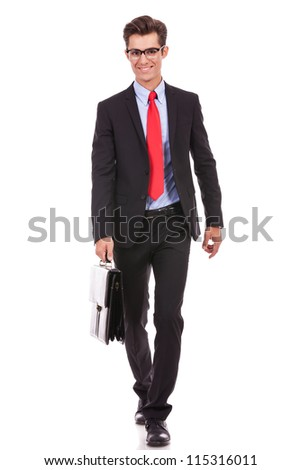 smiling business man wearing glasses is walking with a briefcase - stock photo