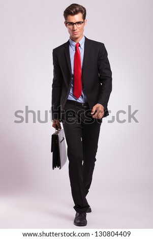 smiling business man wearing glasses is walking with a briefcase on gray background - stock photo