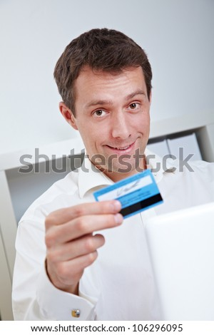 Smiling business man with laptop and credit card in office - stock photo
