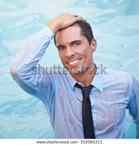 Smiling business man with wet clothes in blue water - stock photo