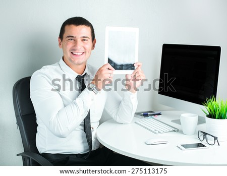 smiling business man working in the office using tablet computer - stock photo