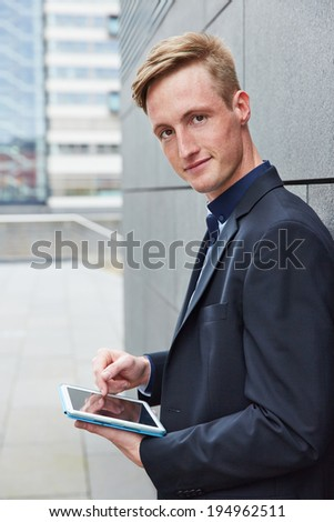 Smiling business man working mobile with tablet computer in the city