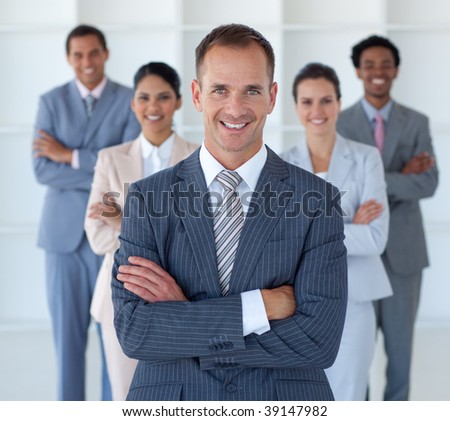 Smiling business manager standing in office leading his team - stock photo
