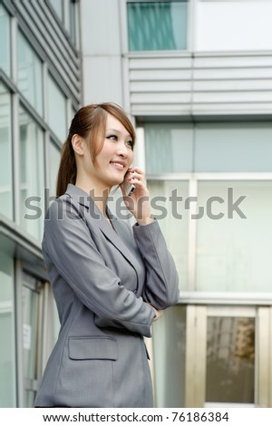 Smiling business manager woman using cellphone, half length closeup portrait outside of modern buildings.