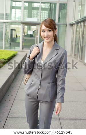 Smiling business manager woman walking after working, half length closeup portrait outside of modern buildings.