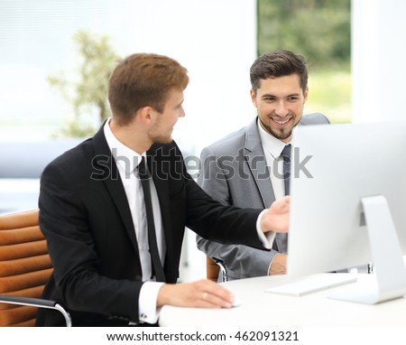 Smiling business men showing something on computer as colleague