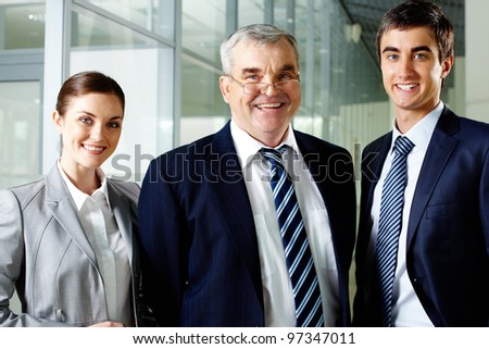 Smiling business partners in suits looking at camera - stock photo