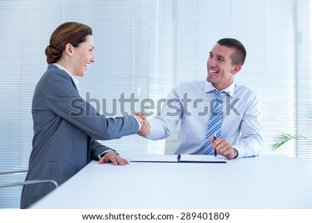 Smiling business partners shaking hand together in an office - stock photo