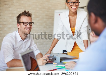 Smiling business partners talking to colleagues at meeting - stock photo