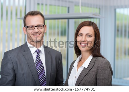 Smiling business partners with a successful confident man and woman posing side by side in the office smiling at the camera - stock photo