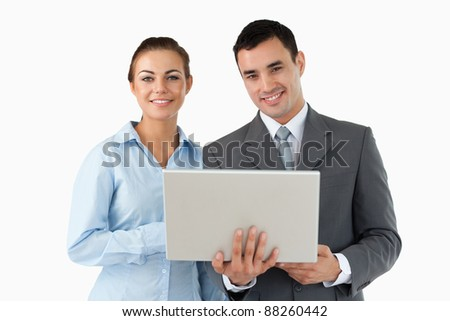 Smiling business partners with laptop against a white background