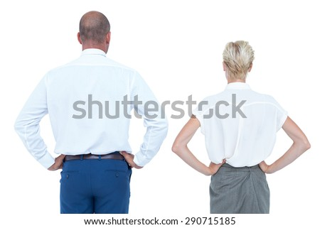 Smiling business people back to the camera with hands on the hips - stock photo