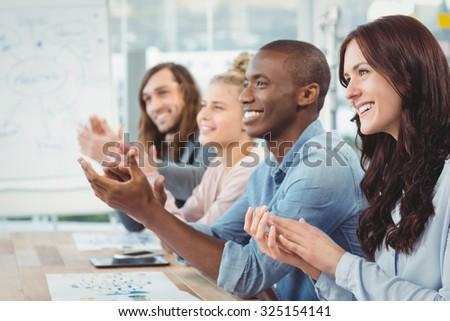 Smiling business people clapping at desk in office - stock photo