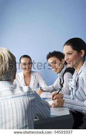 Smiling business people having a meeting and they discussion together on blue background - stock photo