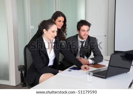 Smiling business people in front of a laptop - stock photo