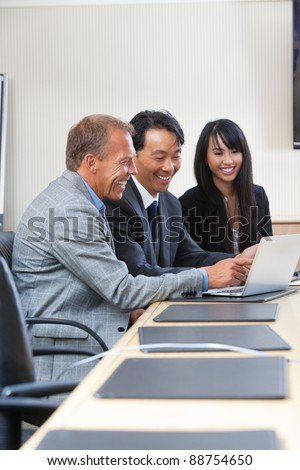 Smiling business people laughing while looking at laptop - stock photo