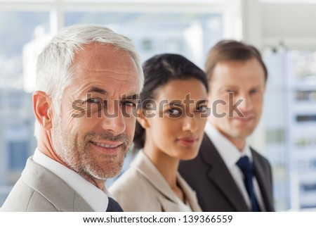 Smiling business people looking in the same way in their office - stock photo