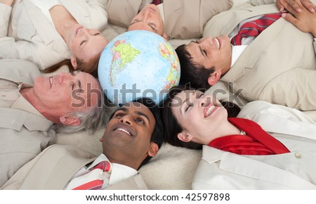 Smiling business people lying in a circle around a globe - stock photo