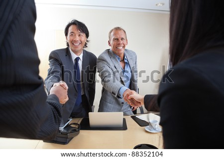 Smiling business people shaking hands in office - stock photo