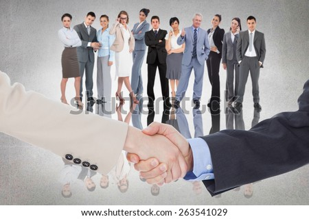 Smiling business people shaking hands while looking at the camera against grey room - stock photo