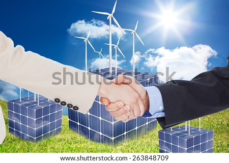 Smiling business people shaking hands while looking at the camera against turbines on cubes made of solar panels