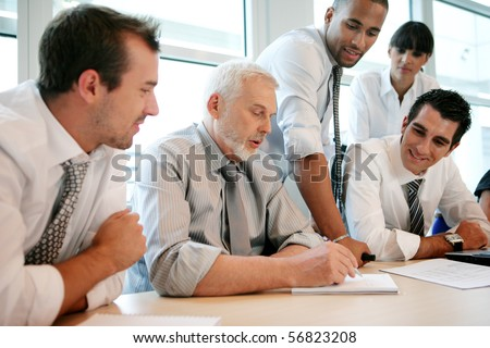 Smiling business people sitting at a desk - stock photo