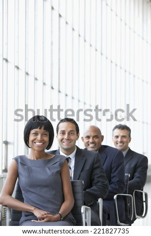 Smiling business people sitting in a line - stock photo