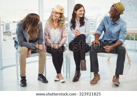 Smiling business people sitting on chair in office - stock photo