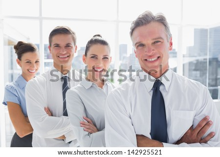 Smiling business people standing together in line in a modern office - stock photo
