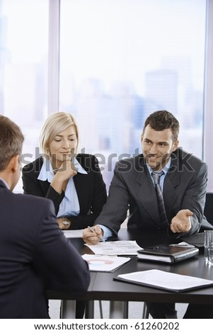Smiling business people talking at meeting in office.? - stock photo