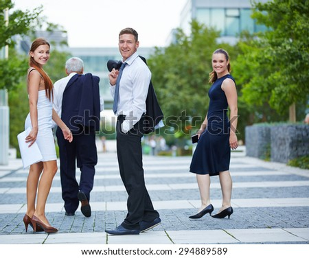 Smiling business people turning around while walking in the city - stock photo