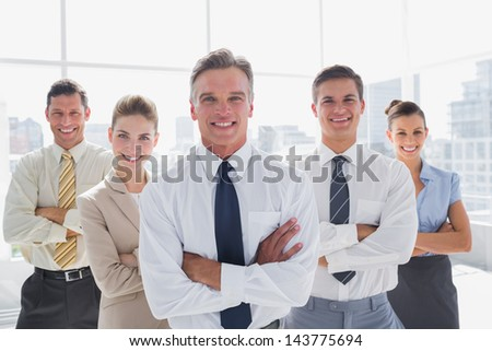 Smiling business people with arms crossed in their modern office
