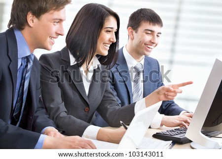Smiling business people with computer in board room - stock photo