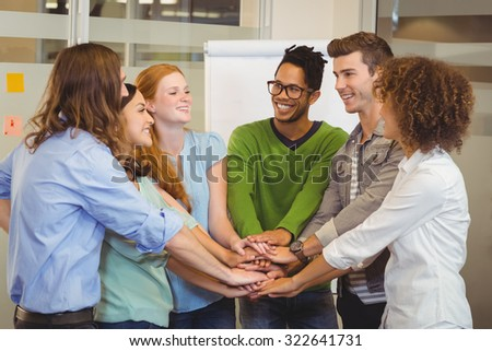 Smiling business people with hand stacked during meeting in creative office - stock photo