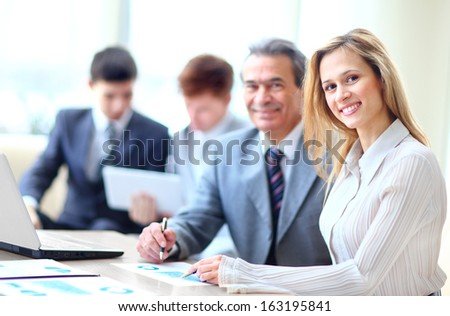Smiling business people with paper work in board room - stock photo