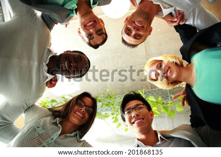 Smiling business people with their heads together representing concept of ftiendship and teamwork - stock photo