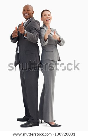 Smiling business people with their thumbs up - stock photo