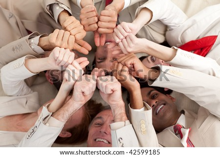Smiling business people with thumbs up lying on the floor in a circle - stock photo