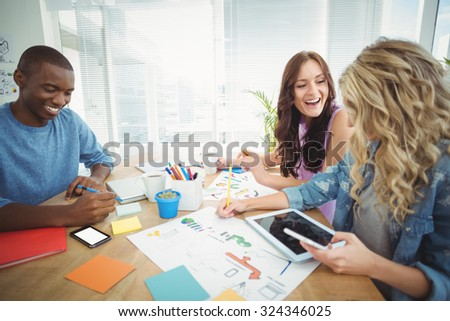 Smiling business people working at desk in creative office - stock photo