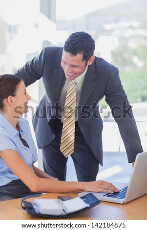 Smiling business people working together with a laptop in the office - stock photo