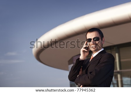 Smiling business person in black suit and sunglasses talking on mobile phone with office building and blue sky in background.