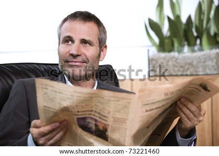Smiling business person in dark suit sitting in office chair reading newspaper and looking up. - stock photo
