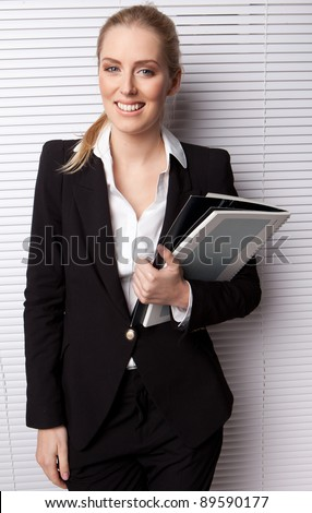 Smiling Business Secretary Holding File standing against a white blind. - stock photo