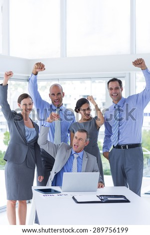 Smiling business team celebrating and looking at camera in the office - stock photo