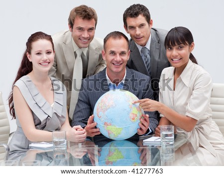 Smiling business team holding a terrestrial globe in the office