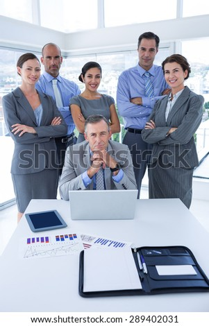 Smiling business team looking at camera in the office - stock photo