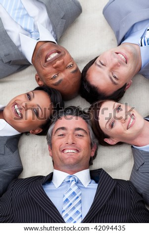 Smiling business team lying on the floor with heads together. Business concept.